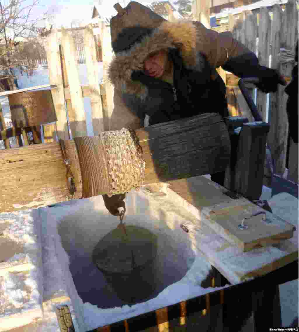 A resident of Temirtau, Kazakhstan, draws water from a partially frozen well.