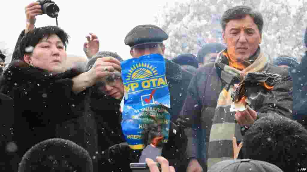 """Болат Әбілев (оң жақтан бірінші) оппозиция жетекшілерімен бірге парламент сайлауы нәтижесіне наразылық ретінде """"Нұр Отан"""" партиясының плакатын өртеп тұр. Алматы, 17 қаңтар 2012 жыл."""