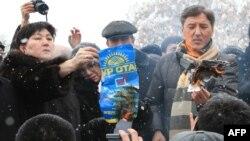 """""""Сайлау әділ өтпеді"""" деп мәлімдеген оппозиция өкілдері парламент сайлауында жеңген партияның жарнама плакатын өртеп жатыр. Қазақстан, 17 қаңтар 2012 жыл."""