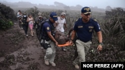 Полицейские эвакуируют пострадавших при извержении вулкана Фуэго. 3 июня 2018 года.