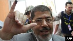 Muslim Brotherhood presidential candidate Mohammed Mursi shows the indelible ink stain on his little finger after voting at a polling station in Zagazig city on May 23.