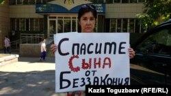 Анжелика Беляева, мать одного из девяти фигурантов дела «о пропаганде терроризма» Азамата Умбеталиева, проводит акцию протеста перед зданием Алмалинского районного суда. Алматы, 24 июля 2019 года.