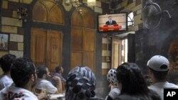 Adamlar Assadyň telewideniýede berlen ýüzlenmesini diňleýärler, Damask, 20-nji iýun.