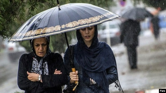 Two women try to keep dry in an autumn rainfall in Rasht, Iran.