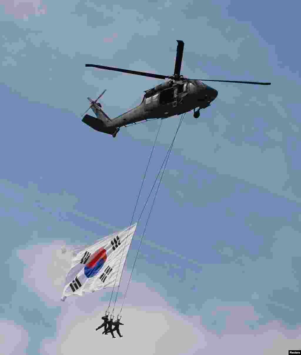 Военнослужащие сил специального назначения, спущенные на тросах с вертолетов во время авиашоу на военном аэродроме к югу от Сеула