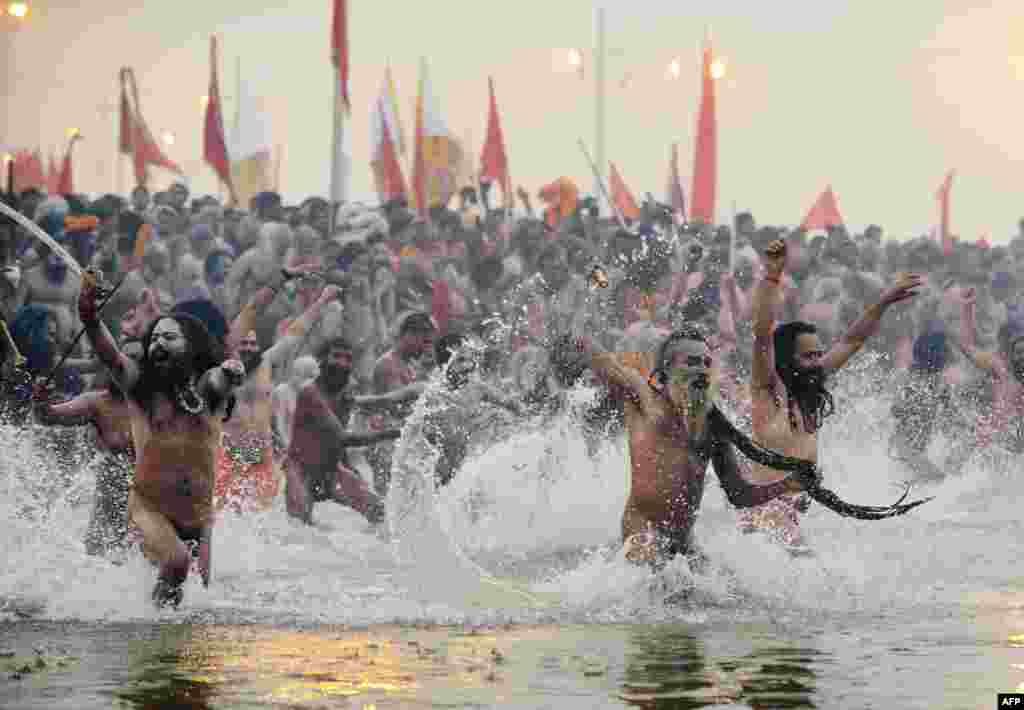 Hundreds of thousands of Hindu pilgrims led by naked, ash-covered holy men stream into the sacred Ganges River at the start of the world's biggest religious festival. The Kumbh Mela in the Indian town of Allahabad will see up to 100 million worshippers gather over the next 55 days to take a ritual bath in the holy waters, believed to cleanse sins and bestow blessings. Before daybreak on January 14, a day chosen by astrologers as auspicious, hundreds of gurus, some brandishing swords and tridents, ran into the swirling and freezing waters for the first bath, signaling the start of events. (AFP/Roberto Schmidt)
