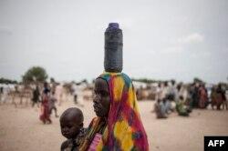 Женщина несет свою дочь в клинику организации ЮНИСЕФ на окраине нигерийского города Майдугури. 30 июня 2016 года.