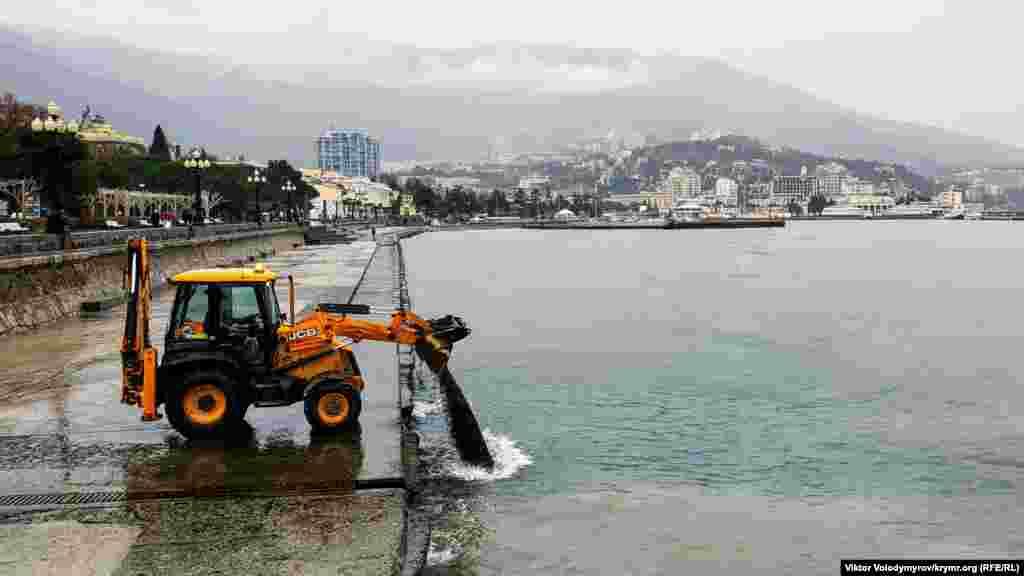 Тракторист чистить набережну від піску, що зібрався після шторму