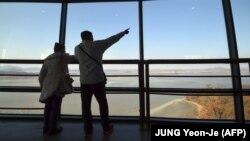 Посетители обзорной площадки на южнокорейской стороне у демилитаризованной зоны – рассматривают территорию Северной Кореи.