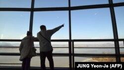 Посетители обзорной площадки на южнокорейской стороне у демилитаризованной зоны - рассматривают территорию Северной Кореи