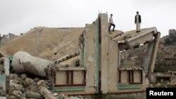 Подростки стоят на развалинах мечети в провинции Саада в Йемене. 28 ноября 2016 года.
