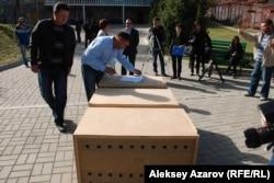 Сотрудники питомника хищных птиц вынесли деревянные ящики с беркутами для передачи в Институт зоологии. Алматы, 20 октября 2014 года.