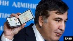 Mikheil Saakashvili Ukrayna Məsləhət Şurasında çalışdığını göstərən vəsiqəni nümayiş etdirir