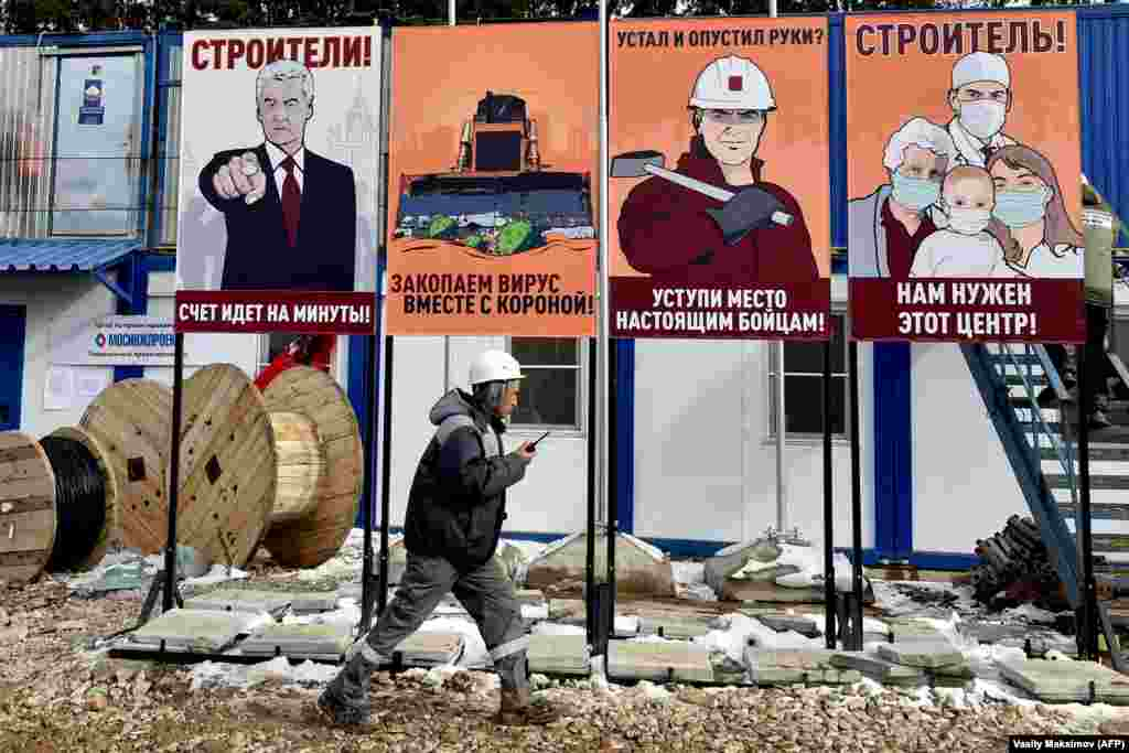 A worker walks past motivational placards designed in the style of Soviet propaganda posters at the construction site of a new COVID-19 hospital outside Moscow on April 1. (AFP/Vasily Maksimov)