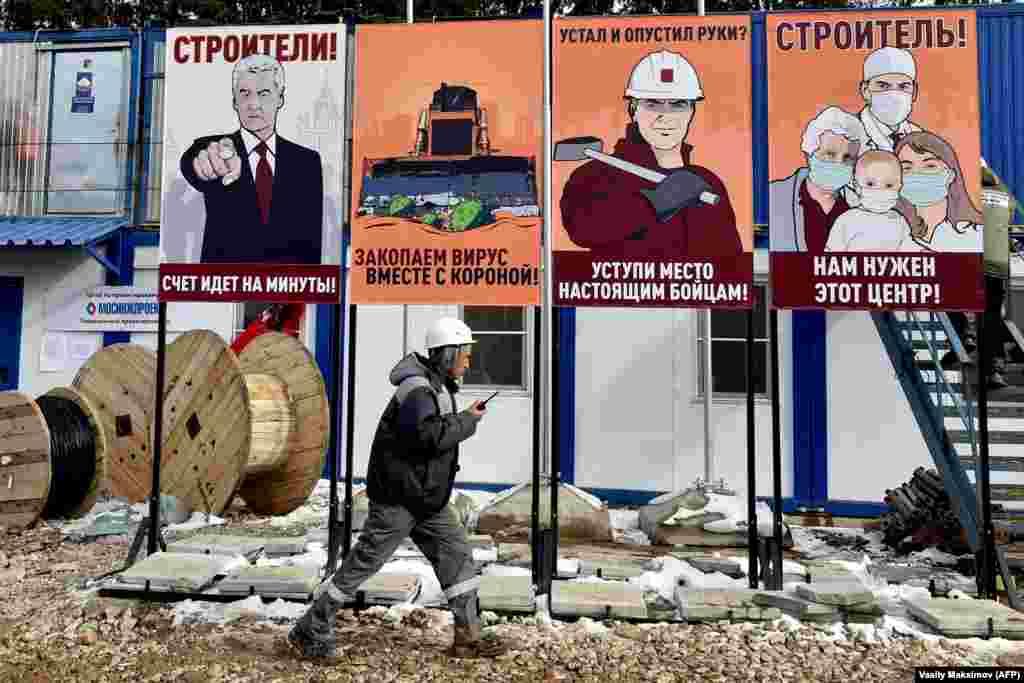 Будаўнік на тле плякатаў на будоўлі новага шпіталя для хворых на COVID-19 у Маскве, 1 красавіка.