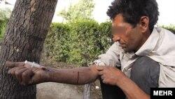 Iran – A man injects drug (addict) in a Tehran park, 16Jun2010