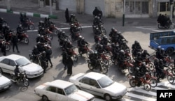 Iranian security forces on motorcycles drive through a street during clashes with opposition protesters in Tehran on December 27, 2009.