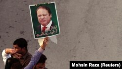FILE: A supporter of the Pakistan Muslim League - Nawaz (PML-N) holds a portrait as he march towards the airport with others to welcome ousted Prime Minister Nawaz Sharif and his daughter Maryam, in Lahore on July 13.