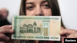 A woman holds a new 200,000 Belarusian ruble note (approximately $24.48) during a presentation to the media in Minsk on March 12.