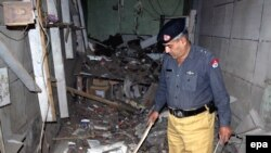 A police official inspects a damaged music shop after a bomb explosion in Charsadda, a town in the Northwest Frontier Province, in 2009.