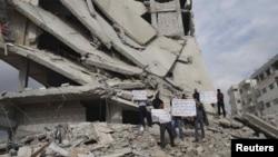 Әскери іс-қимылдардан қираған ғимарат жанында президент Башар әл-Асадтың билігіне қарсы акцияда тұрғандар. Дамаск маңындағы Ербен кенті. 9 қараша 2012 ж.