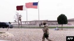 Американский солдат проходит перед штабным офисом, из которого координировались военные действия в Ираке. 26 марта 2003 года