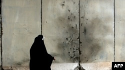 Two Iraqi women walk past a damaged blast wall in Baghdad, July 13, 2009