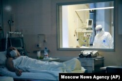 A doctor observes through a glass window the condition of a coronavirus patient in Moscow's Sklifosovsky emergency hospital on March 25.