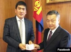 Управляющий делами президента Монголии вручает служебное удостоверение советнику президента Жандосу Шарипу.