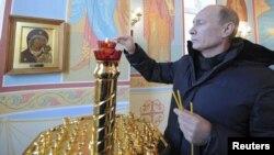 Премьер-министр России Владимир Путин зажигает свечу в часовне во время визита в Хакасию. 19 декабря 2011 года.