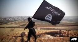 """""""Ислам мемлекеті"""" (ИМ) экстремистік ұйымының YouTube желісіне жариялаған видеосынан алынған скриншот. (ИМ мүшесі ұйымның туын көтеріп тұр)"""