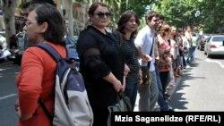Около ста студентов и преподавателей в знак протеста, взявшись за руки, выстроились в живую цепь на разделительной линии проезжей части в центре Тбилиси