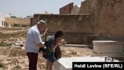 Франко-тунисская еврейская пара Ричард и Дебора Хакун посещают могилу своего родственника на кладбище за большой синагогой тунисской еврейской общины на острове Джерба. 27 мая 2016 года.