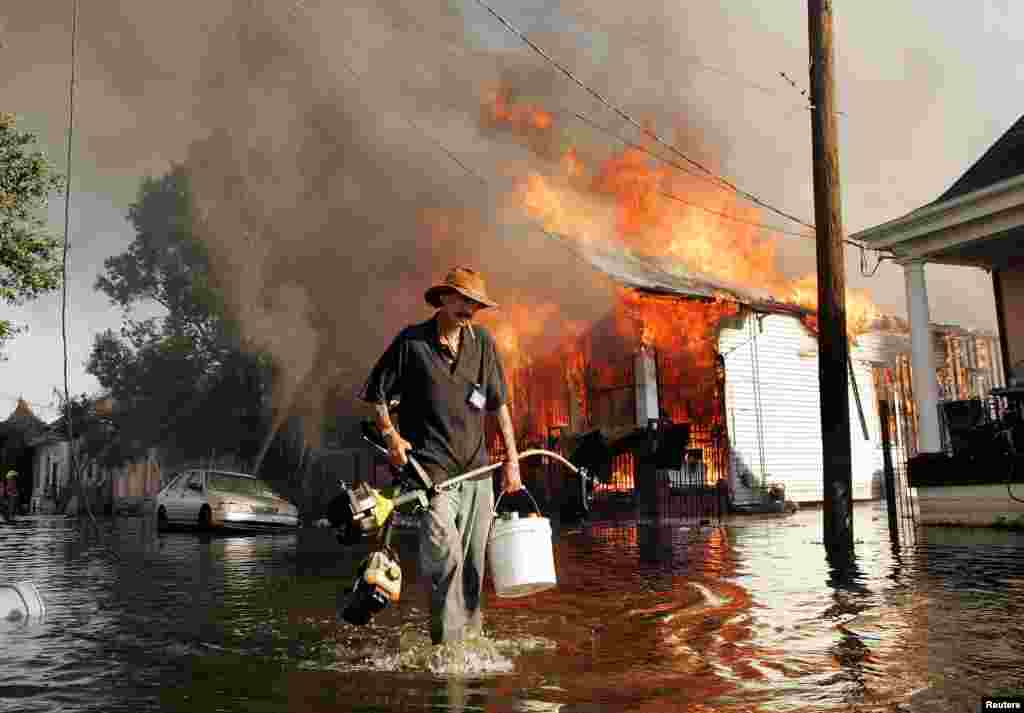 A man walks through floodwater as a home burns during the aftermath of Hurricane Katrina in New Orleans on September 6.