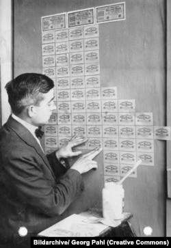 A German man using worthless banknotes for wallpaper in 1923.