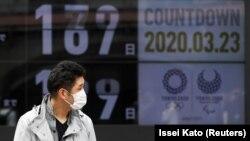 Токио олимпиадасының эмблемасы жанында тұрған маскадағы адам. Токио, 23 наурыз 2020 жыл.