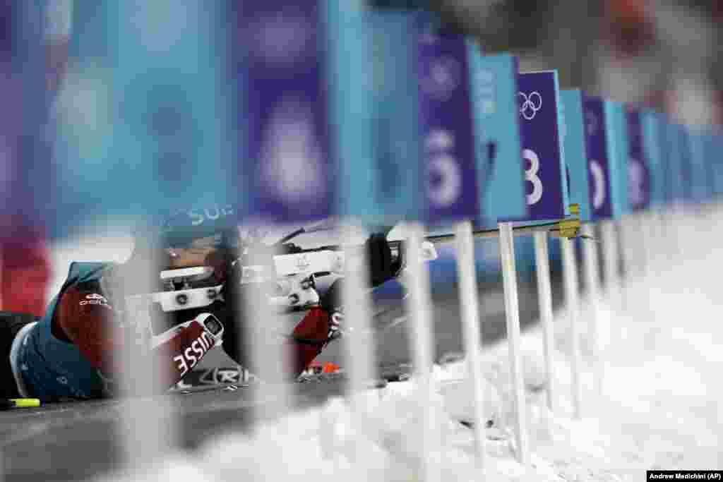 Биатлон: Аита Гаспарини из Швейцарии настраивает свою винтовку во время соревнований по биатлону