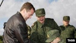 Президент России Дмитрий Медведев дарит Николаю, сыну белорусского коллеги Александра Лукашенко, позолоченный пистолет с кобурой. Беларусь, Обуз-Лесновский полигон, 29 сентября 2009 года.