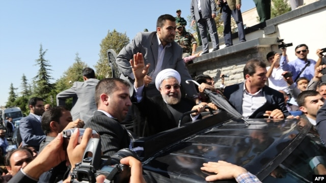 Rohani waving to supporters after arriving in Tehran last month following his ice-breaking trip to New York.