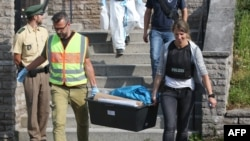 Police officers leave after conducting a search at a refugee shelter on July 25 where a 27-year-old Syrian migrant who set off an explosive device near an open-air music festival had stayed, in Ansbach.