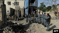 Afghan policemen inspect the site of a seemingly botched suicide attack in Kabul on May 25.