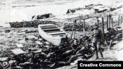 Японский солдат стоит на берегу реки Янцзы, усеянном телами тысяч убитых китайцев. Декабрь 1937 года