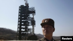 A North Korean soldier stands guard in front of the Unha-3 (Milky Way 3) rocket sitting on a launch pad.