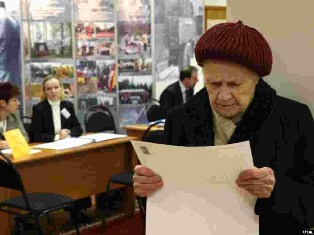Избирательный участок, Москва. Избирательница изучает бюллетень.