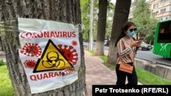 Девушка в защитной маске идет по улице Алматы. 22 июня 2020 года.