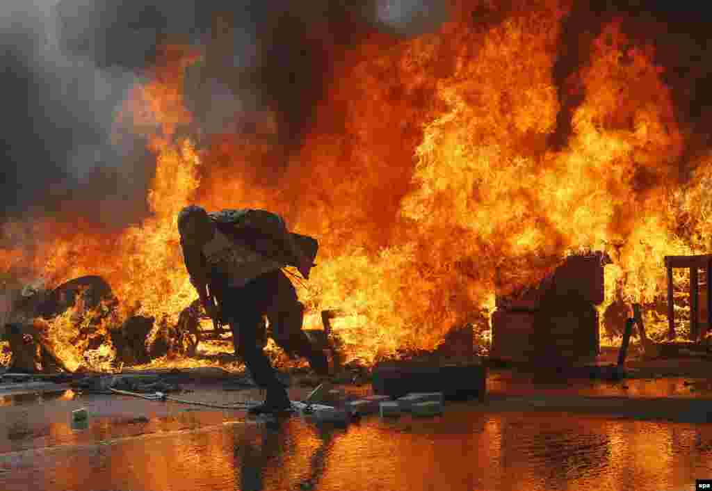 An activist runs from a burning barricade on Khreshchatyk Street near Independence Square, also known as the Maidan.