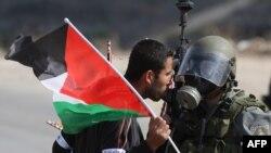Një protestues palestinez i ofrohet ushtarit izraelit gjatë një protese në fshatin Nabi Saleh, në Rripin e Gazës