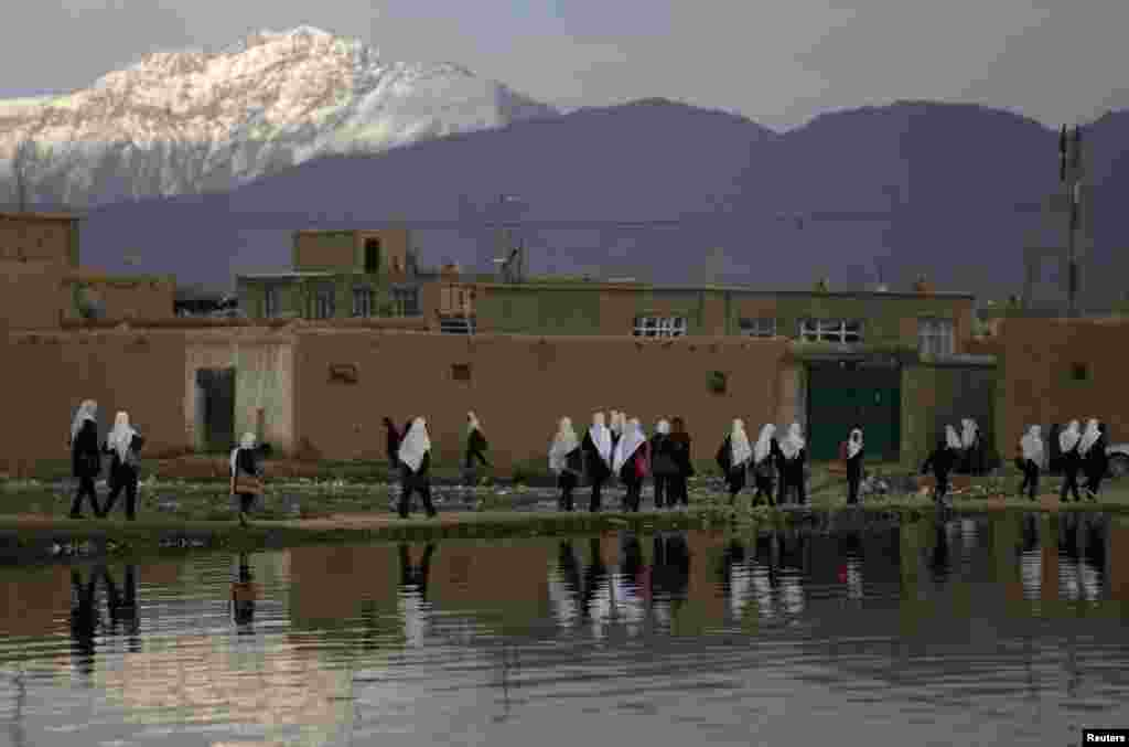 Afghan students walk along a lake as they head home in Kabul. (Reuters/Mohammad Ismail)
