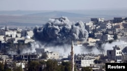 A presumed air strike by the U.S.-led coalition strikes the Syrian town of Kobani on October 23.
