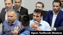Injured Social Democrat leader Zoran Zaev is escorted out of the parliament in Skopje on April 27.